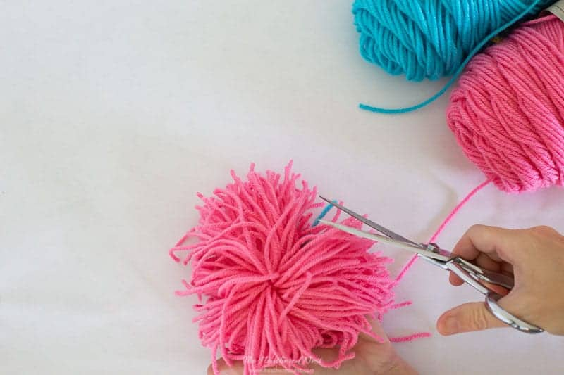 trimming yarn to uniform length all around as described in this how to make yarn pom poms tutorial.