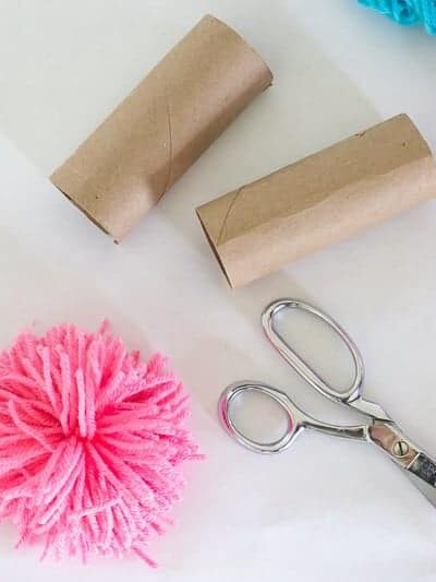 The little trick in this post is so helpful! Great step by step tutorial and video for how to make yarn pom poms with toilet paper rolls or a paper towel roll! #pompom #pompoms #howtomakepompoms #yarnpompoms #pompomcrafts #pompomdiy #DIYyarnpompoms #pompomideas #pompommaking #pompomtutorial