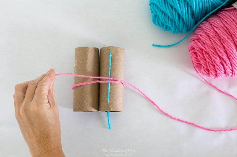 starting to loop yarn around toilet paper rolls as described in this DIY tutorial for how to make yarn pom poms.