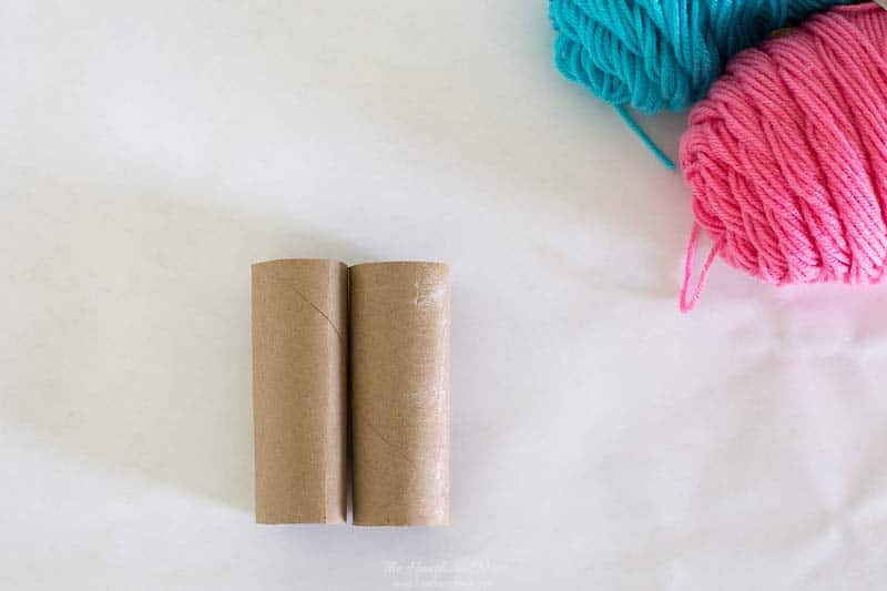 2 toilet paper rolls. basic supplies pictured for making yarn pom poms. #pompom #pompoms #howtomakepompoms #yarnpompoms #pompomcrafts #pompomdiy #DIYyarnpompoms #pompomideas #pompommaking #pompomtutorial
