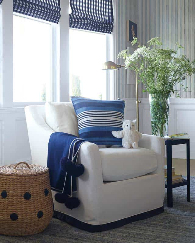 white rocker with navy pom pom throw blanket, striped coastal pillow, gingham roman shades and rattan blanket in nautical nursery
