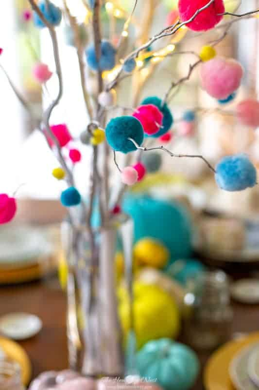 closeup of DIY pom pom branch centerpiece with lighted birch branches