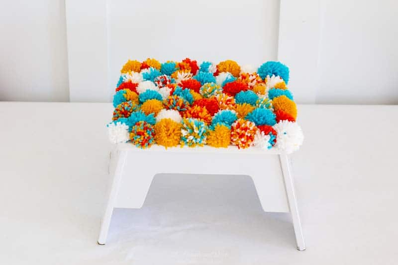 Make a soft & fluffy DIY pom pom footstool. This project is so easy, and turned out so cute!! #footstool #pompoms #DIY #stepstool #DIYpompomcraft #pompomcrafts #pompomcraftideas #pompomprojects