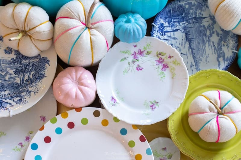 closeup of mix and match colorful plates, colorful DIY fabric pumpkins and spray-painted pumpkins for a colorful thanksgiving table