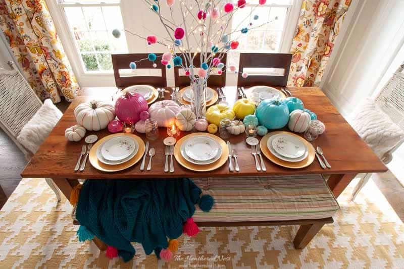 a non-traditional thanksgiving tablescape with pom pom branches, painted and fabric pumpkins and bright, happy hues