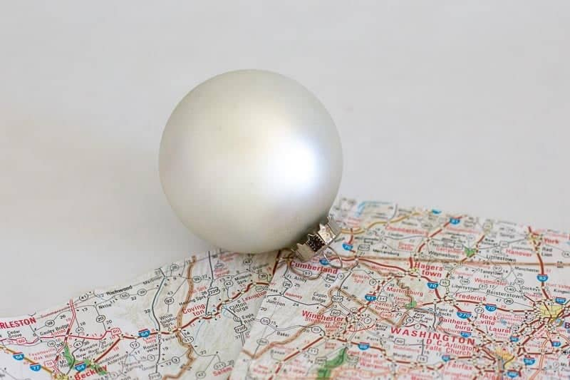 Basic glass ball ornament or shatterproof ball ornament and a map are the basic supplies needed for this DIY ornament craft. Map Homemade Christmas Ornaments are easy to make (but no one will guess-shhh!). Mark a hometown or other special place & give your loved one the world.
