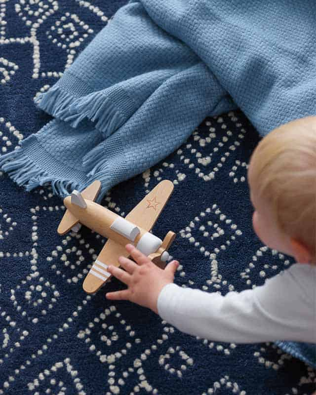 Baby on coastal patterned rug with blue fringe blanket and wood airplane toy