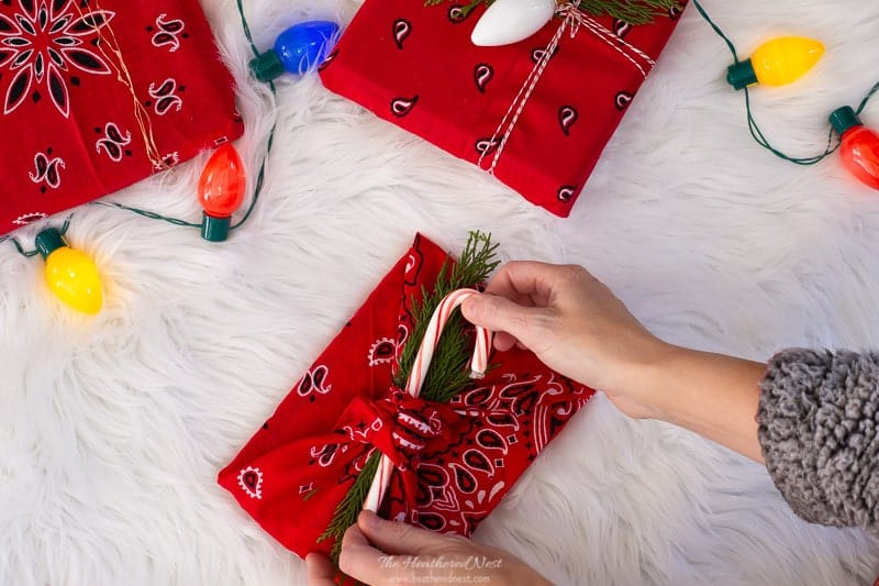 placing candy cane topper on a Christmas gift wrapped with a red bandana