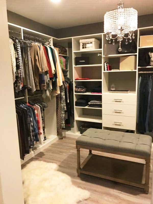 Playroom converted into master dressing room with glam touches and white closet system integrating open shelving, drawer space, double hung clothing bars, valet bar and more.