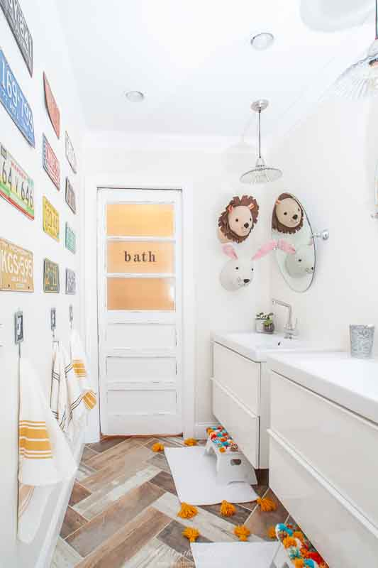 DIY pom pom foot stool project in a kids bathroom with floating double vanities. nice pop of color with this inexpensive DIY bathroom project