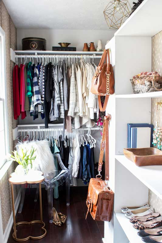 Closet Organizer Ideas: In this master closet you can see doubled up hanging racks for doubling the hanging space. Shallow open shelving used for shoes and accessories, hooks for hanging bags.