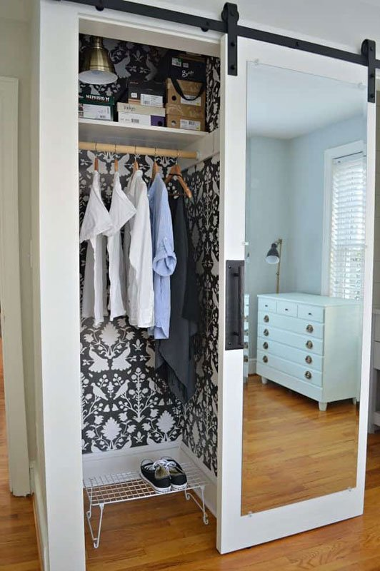 Small closet with sliding, mirrored barn door and bold black and white damask wallpaper within. If you've been scared to try wallpaper, a closet is a great place to give it a go!