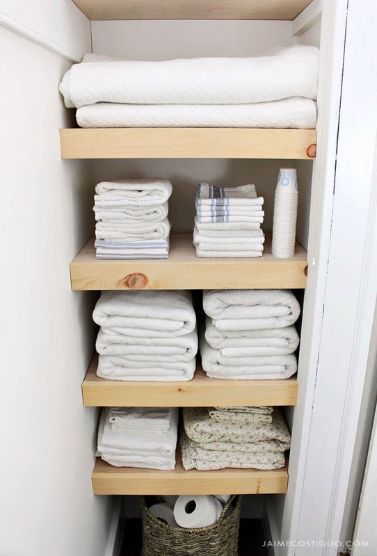 A simple DIY wood shelving system to organizer a small linen closet