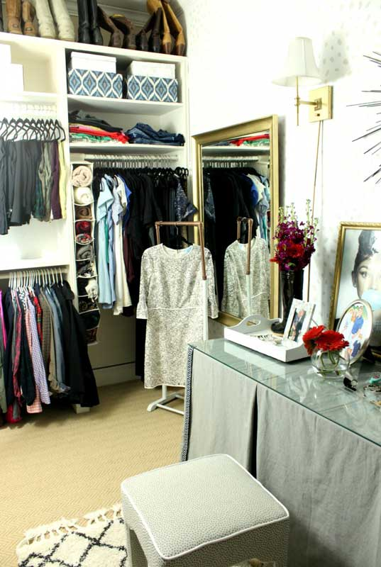 Closet Organizer Ideas: Master closet makeover with glam touches. Seasonal shoes and boots stored on top shelf. A portable clothes rack is used for outfit planning and packing.