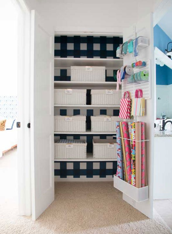 Organized crafting closet, wrapping center with labeled bins, ribbon storage in wire shelving, back of door wrapping zone and buffalo check wallpaper.