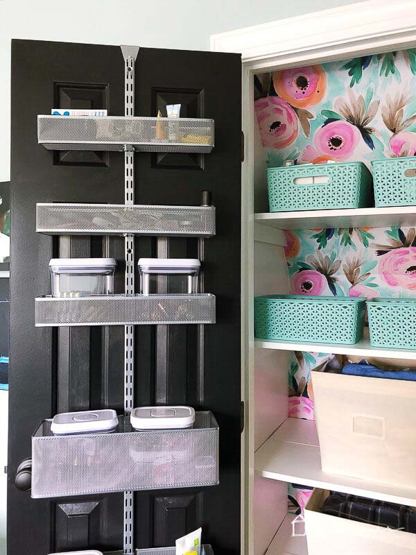 Organized linen closet with dark painted door, back of door organizer and matching bins and baskets on open shelving. Bright floral wallpaper in back of closet.
