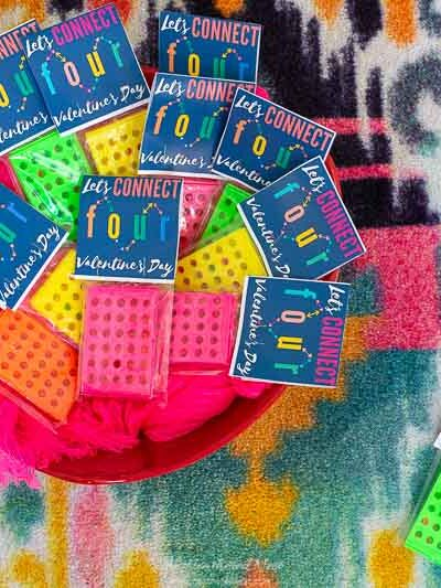 Mini-Connect Four games with free printable valentines for kids seen in red bowl on colorful carpet