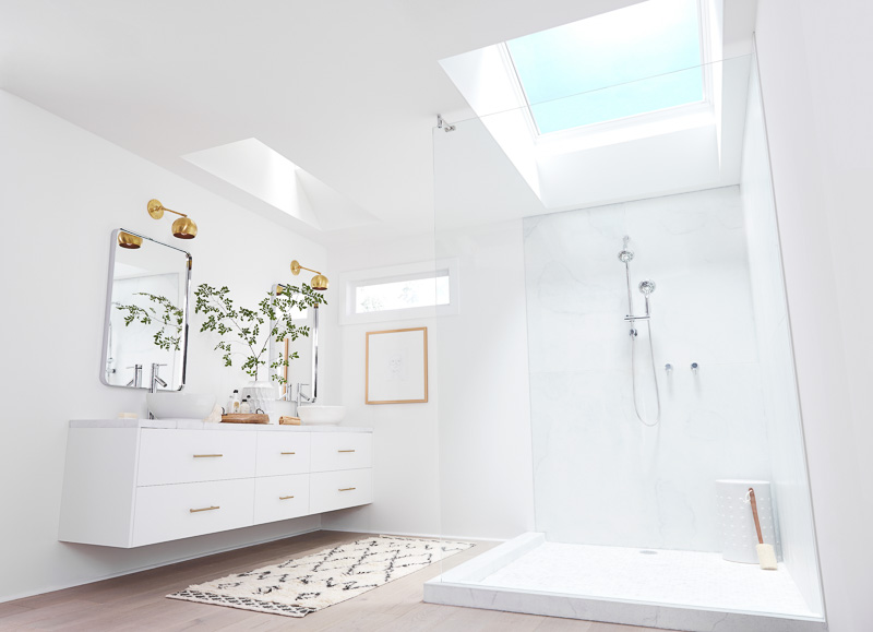 White master bathroom with seamless glass enclosure, floating modern double vanity and Velux skylights