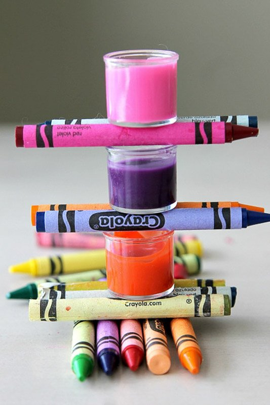 Recipe for 2-ingredient DIY lipgloss using melted crayons seen stacked with three small lipgloss containers with colorful lip balm