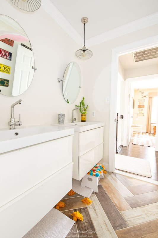 kids hall bathroom with faux wood tile, floating double vanities, license plate gallery wall. Tour 15 Colorful Homes in this spring colorful home tour!