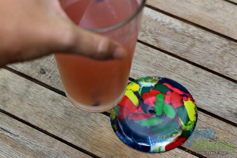 A DIY coaster made from melted crayons seen on a wood table and a drink being placed or taken off the colorful coaster