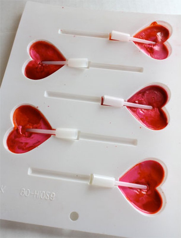 Learn how to make melted crayon pencil toppers. Image of melted red crayon wax in heart-shaped forms with pencil toppers in them during the DIY process