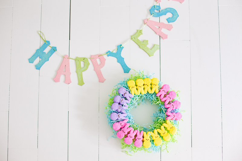 DIY marshmallow Peeps Wreath on white planked background with Happy Easter banner