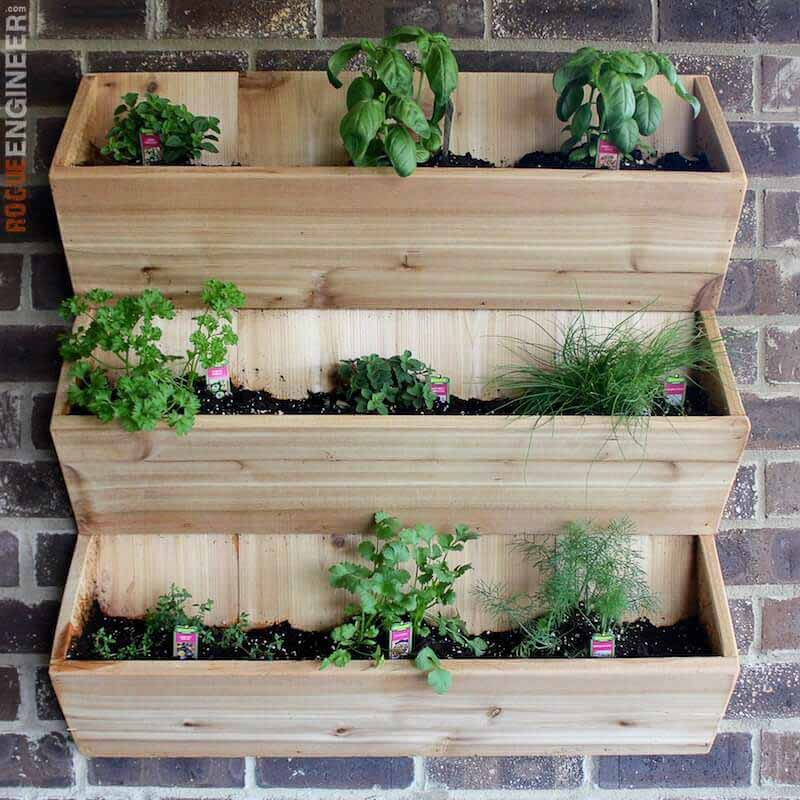 Three-tiered wood vertical planter hanging on a brick wall