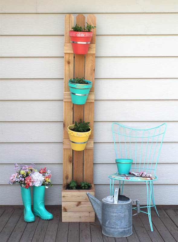 Colorful pots are tiered onto a wood fence picket backboard with small wood planting box at base to create a free-standing DIY vertical planter