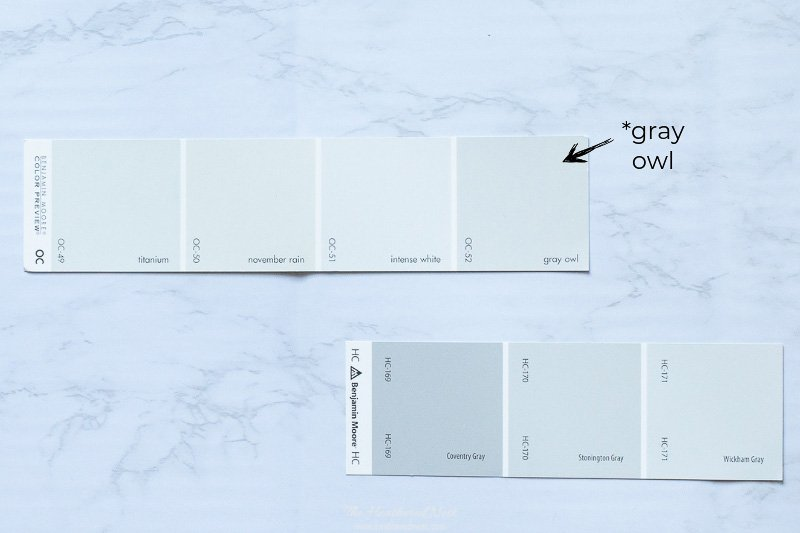 Benjamin Moore Gray Owl paint chip on a marble surface next to another popular gray paint card including Stonington Gray, Coventry Gray and Wickham Gray.