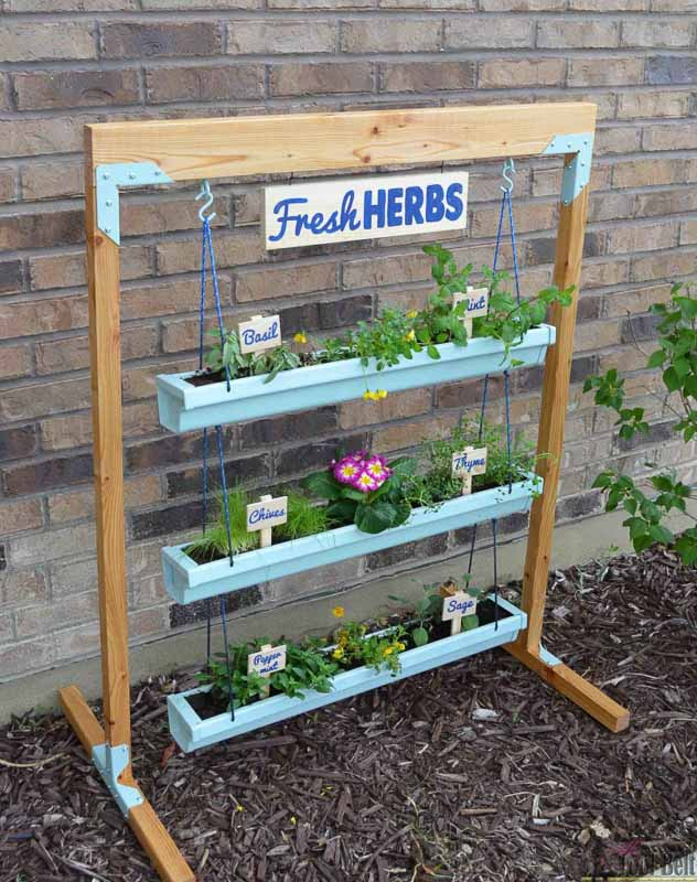 Vertical garden made with three tiers of rain gutter hung stacked and horizontally with s-hooks from the free-standing wood frame.
