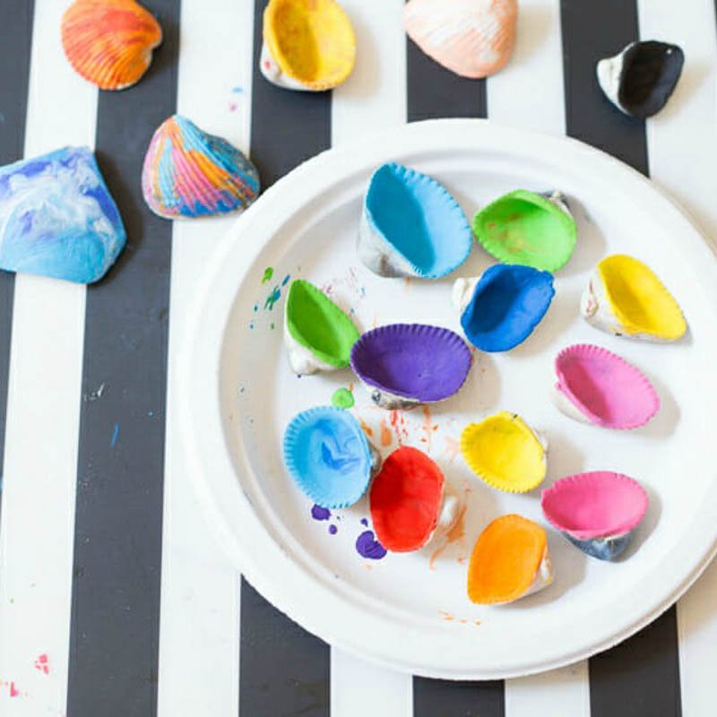 A fun craft for kids - melted crayon seashells. Image of many colorful seashells on a paper plate with black and white striped background