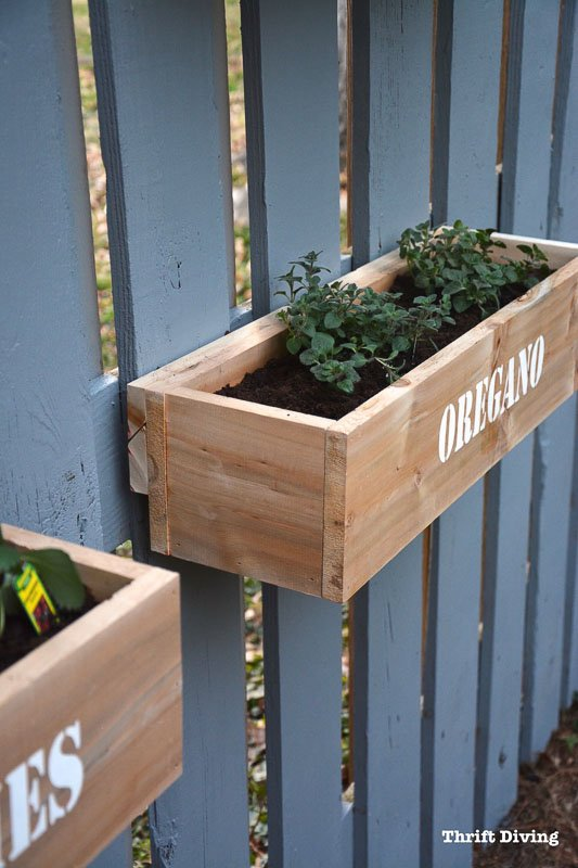 DIY wood planter boxes attached with french cleat to blue/gray fence