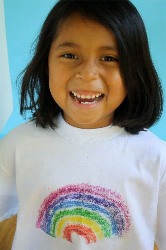 smiling girl wearing a DIY melted crayon t-shirt with rainbow print