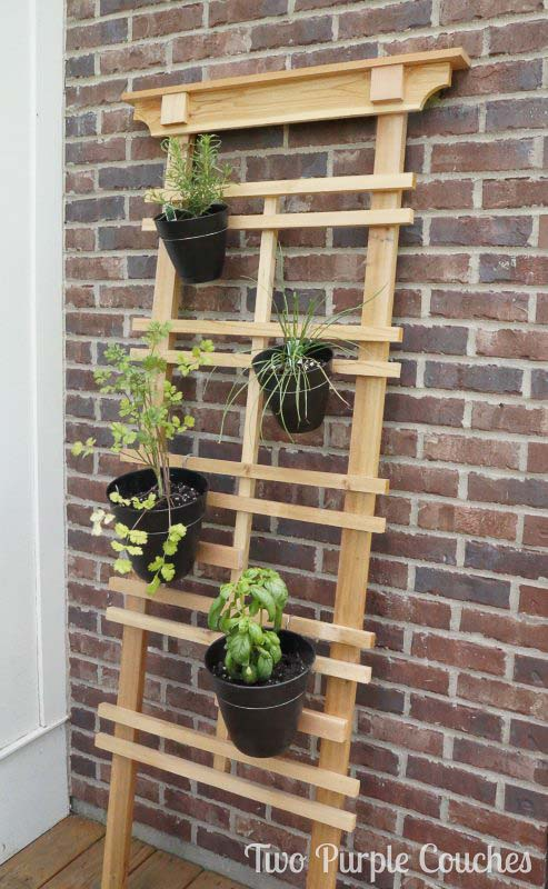 A simply constructed wood trellis leans against a brick wall. Potted herbs are attached to the wood trellis to create an easy DIY vertical garden.