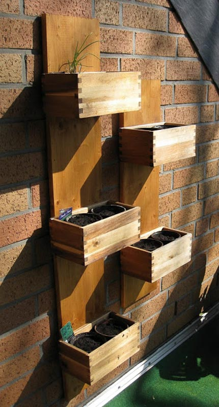 Vertical garden Ikea hack using Bjuron wood planters attached to a piece of wood which leans against a vertical surface.