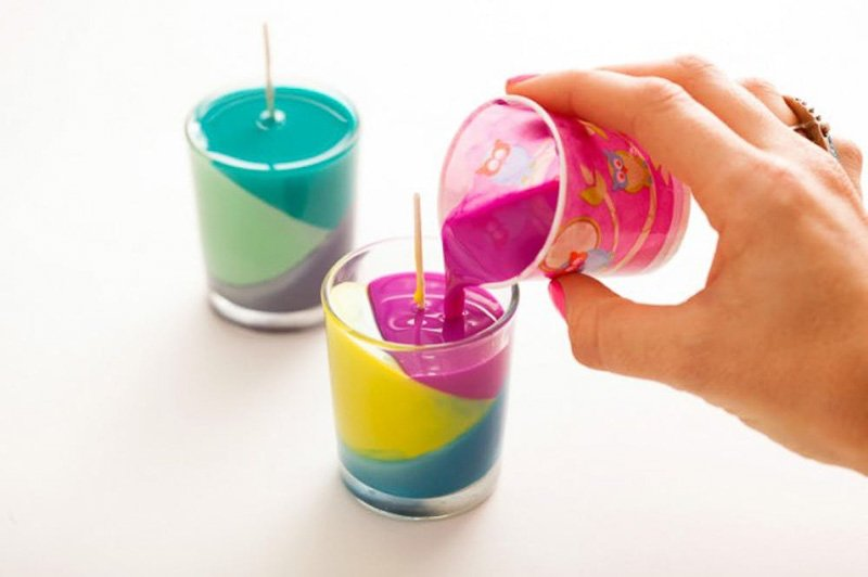 Pouring hot pink wax into glass votive to make DIY color block candle from crayons