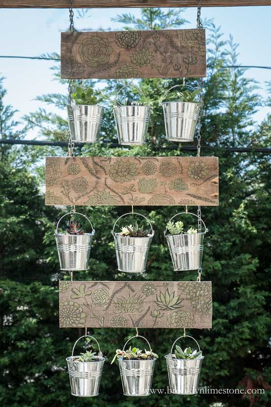 Vertical garden hanging from chain constructed of decorative embellished wood with metal pots
