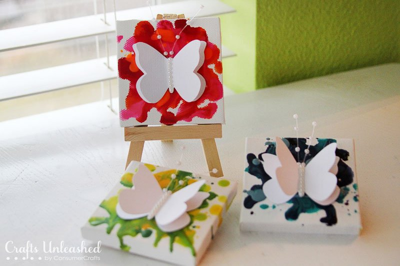 Three mini canvases with colorful melted crayon wax and 3D paper butterfly embellishment