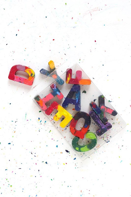 DIY ABC forms from melted crayons. Image of multi-colored letters resting on white surface with colorful crayon shavings