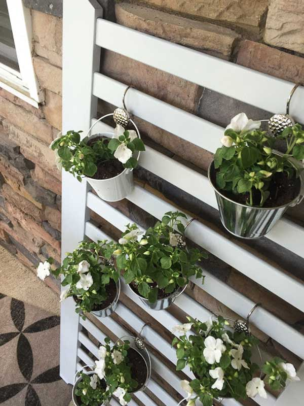 Old crib slat mattress frame upcycled into a vertical planter with metal pails hung with shower curtain hooks