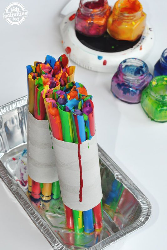 Use old crayons to create colorful magic wands for kids seen bundled together in a bread pan on a white table