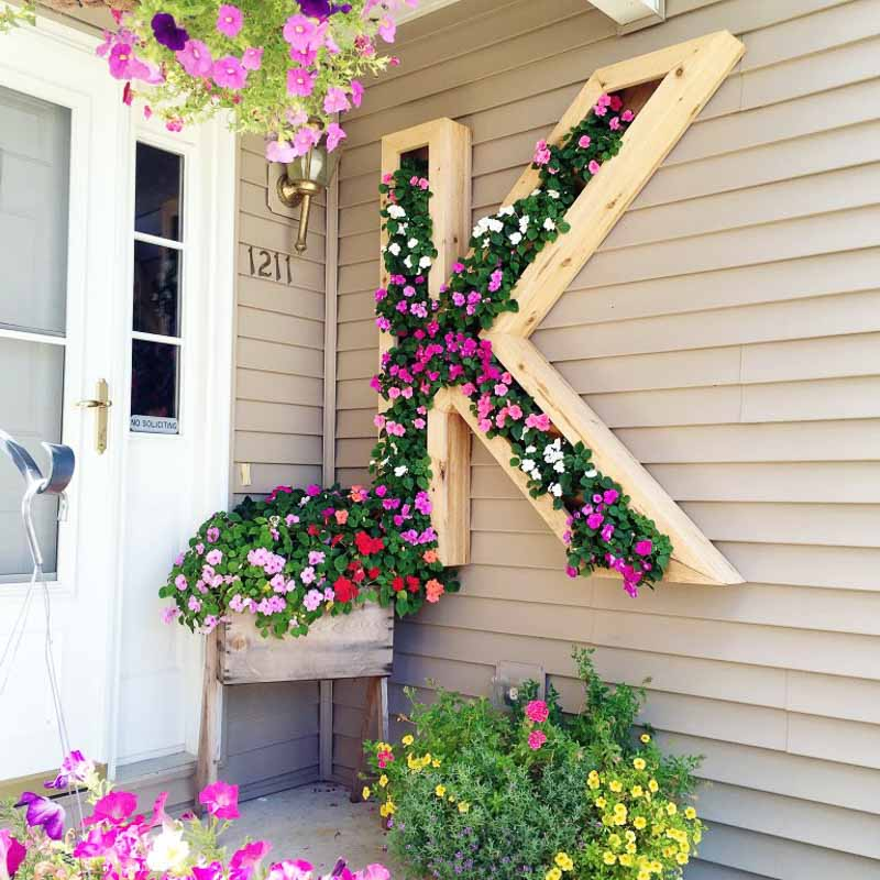 large-scale DIY wall planter vertical garden in shape of monogram, this one is the letter K and planted with annuals.