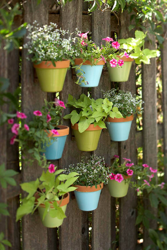 A fun and simple way to garden and add color to an outdoor space. Attach colorfully painted terra cotta pots to a fence.