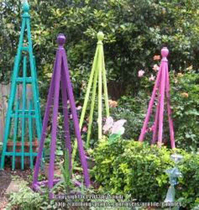 DIY garden pyramids in an outside garden for growing vine plants such as cucumbers and tomatoes.