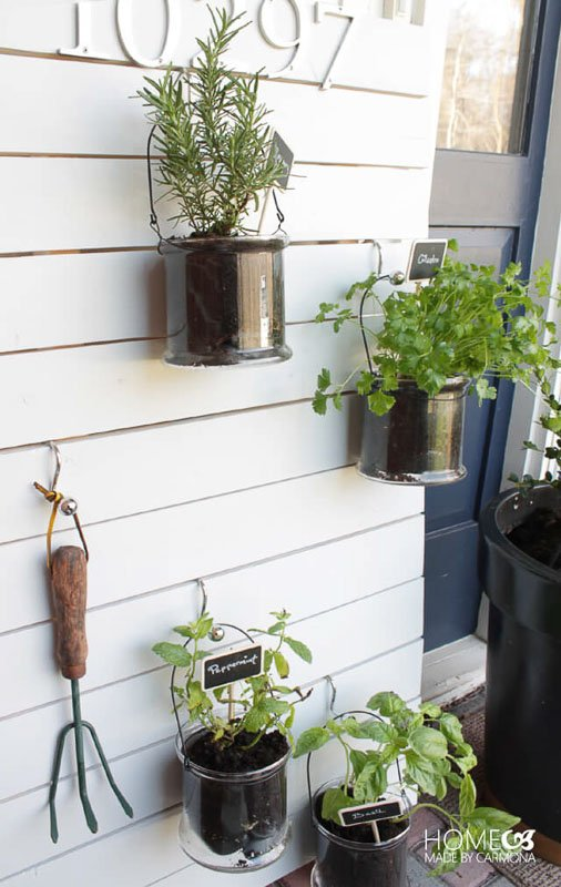 white slatted wood frame with kitchen herbs hung in clear pails with s-hooks in front of home