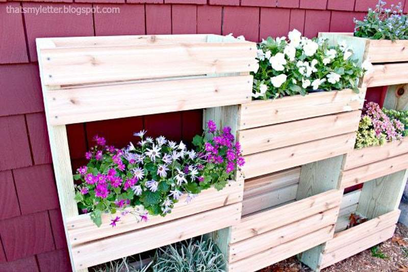Wood tiered garden against red shingled home. Planter resembles wood crates attached together. Here planted with annuals