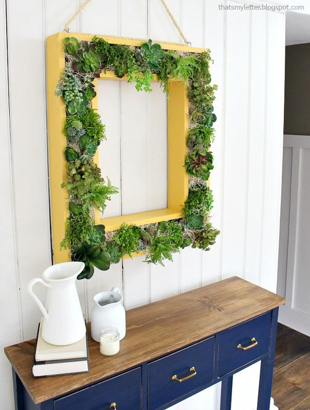 Wood frame square pictured frame vertical succulent garden. Yellow frame seen inside a home with white planked walls and blue buffet table