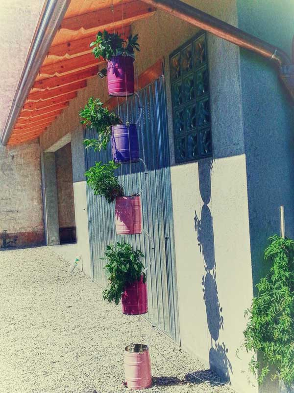 Recycle old keg containers to create a hanging vertical garden like this one seen suspended from the eaves of a roof.