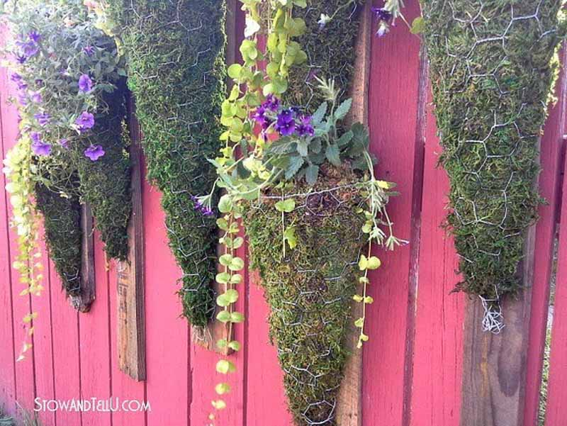 cornucopia-shaped planters made from chicken wire and filled with soil and moss for planting flowers on a red fence.